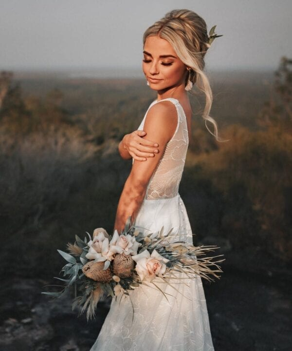 Bride poses with roses and Australian native bouquet