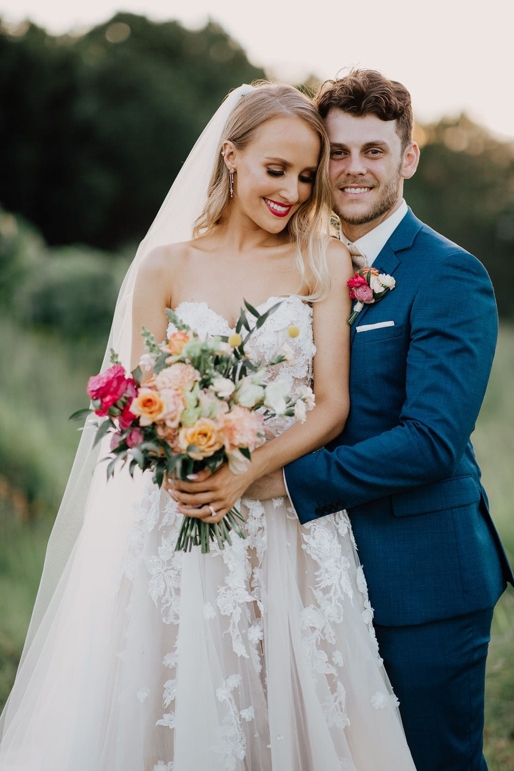 Bride holds bouquet whilst standing with groom