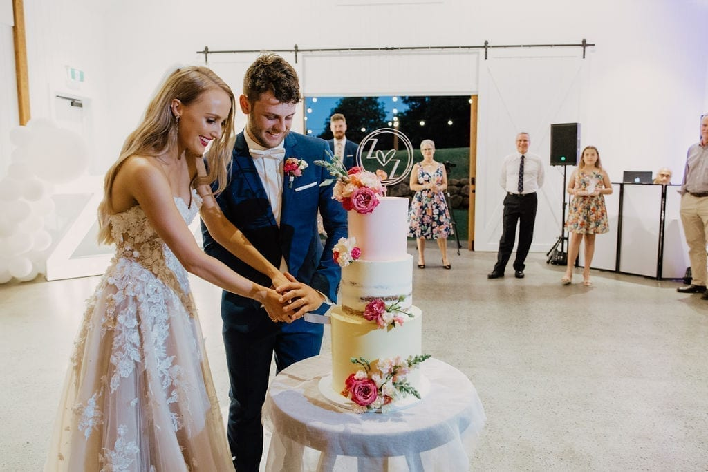 Newly weds cutting their cake by Milk and Honey Cake Creative